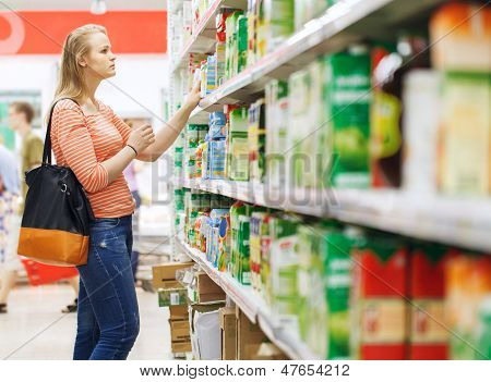 Young woman shopping for juice in supermarket