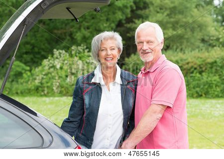 Senior couple standing at a black car
