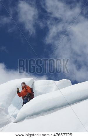 Low angle view of a male hiker standing on ice chunks