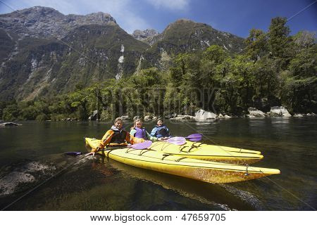 Three young people kayaking in the lake with mountains in background