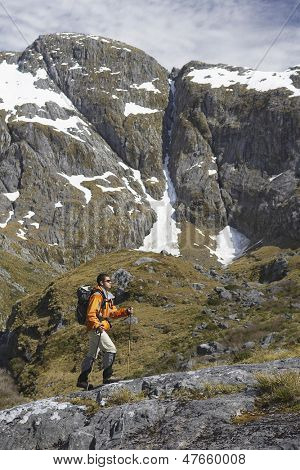 Full length side view of a male hiker climbing trail in steep mountains