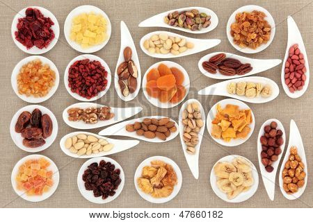 Nut and fruit selection in white porcelain bowls over hessian background.