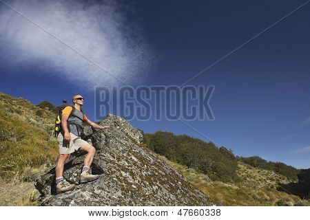 Low angle view of a bald man climbing up boulder in forest valley