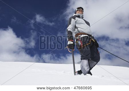 Low angle view of a male mountain climber standing on snowy slope with safety line attached