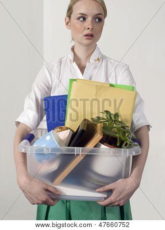 Female office worker carrying personal belongings indoors