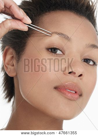 Closeup of a young woman plucking eyebrow against white background