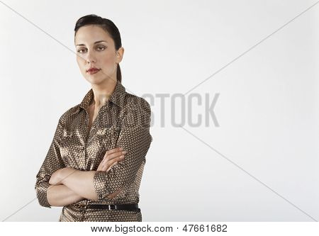 Portrait of a confident businesswoman with arms crossed standing against white background