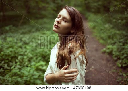 Unhappy Girl Standing In The Middle Of A Forest