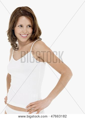 Young smiling woman in camisole with hands on hip against white background