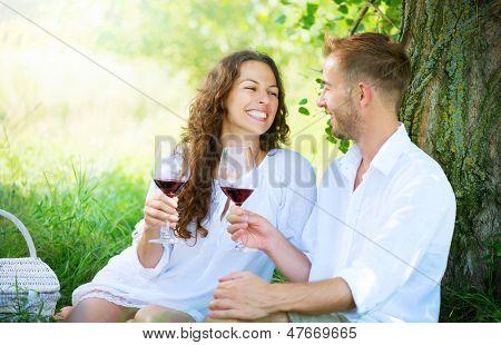 Hermosa pareja joven haciendo un Picnic en el campo. Familia feliz al aire libre. Rel sonriente hombre y mujer