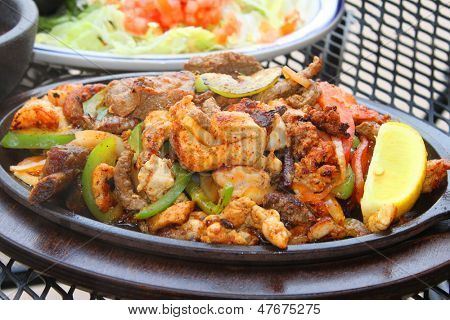 Hot chicken, beef and shrimp fajitas on a skillet
