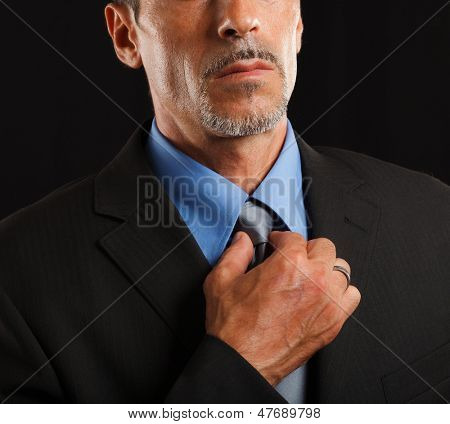 Businessman adjusting his necktie