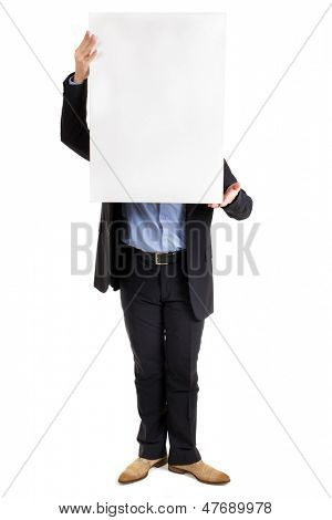 Businessman holding up a blank white rectangular sign or placard with copyspace for your text in front of his face concealing it, isolated on white