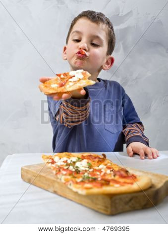 Young Boy Eating Pizza