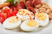 stock photo of boil  - Hard boiled chicken eggs with beans and sausage served for breakfast - JPG