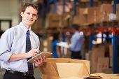 Manager im Warehouse Check-Boxen, die mit digitalen Tablet