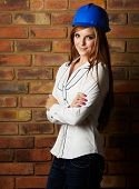 picture of blinders  - Beautiful young adult caucasian woman wearing a blue safety hat black pants and a white shirt in front of a brown brick wall with crossed arms - JPG