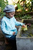 stock photo of wet pants  - Little four year old boy in a blue outfit playing with paper boats in a small outdoor water fountain - JPG