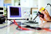 stock photo of  multimeter  - soldering electronic parts on a printed circuit board - JPG