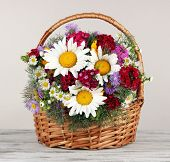 Beautiful bright flowers in wicker basket on table on gray background