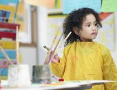 Cute little girl holding paintbrush in art class
