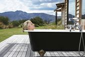 stock photo of bathtime  - Side view of a young blond woman in bathtub on porch against mountains - JPG