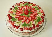 image of dizziness  - cake with strawberries kiwi and mint green and almonds. close to
