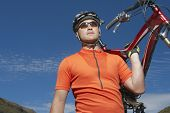 pic of spandex  - Male cyclist carrying bike against blue sky - JPG