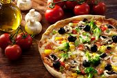 foto of crust  - freshly prepared vegetarian pizza with brokkoli, pepper, mushrooms, onion rings, tomatoes and olives