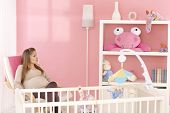 stock photo of expecting baby  - Pregnant mother sitting in armchair in pink baby - JPG
