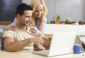 stock photo of fondling  - Young couple browsing internet at home - JPG