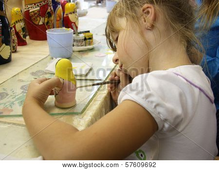 Little girl painting a matrioshka russian doll