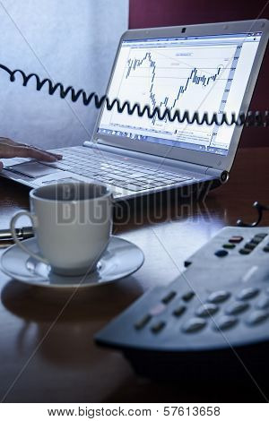 Close-up of female calling by phone in front of a laptop with a coffee in the office