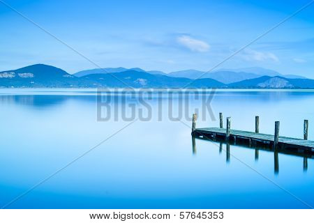 Wooden Pier Or Jetty And On A Blue Lake Sunset And Sky Reflection On Water. Versilia Tuscany, Italy poster