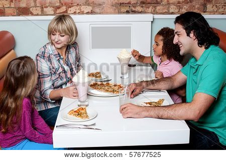 Cheerful Family Of Four Enjoying Breakfast