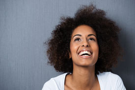 picture of afro hair  - Laughing African American woman with an afro hairstyle and good sense of humour smiling as she tilts her head back to look into the air - JPG