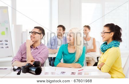 business, education, photography, office and startup concept - smiling creative team with photocamera listening to lecture in office