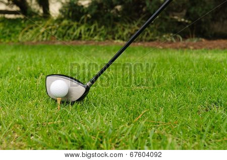 Golf ball on a tee with #3 wood, driver or pitching wedge