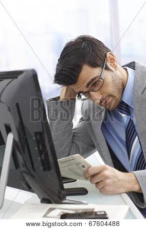 Troubled businessman reading newspaper, financial news.
