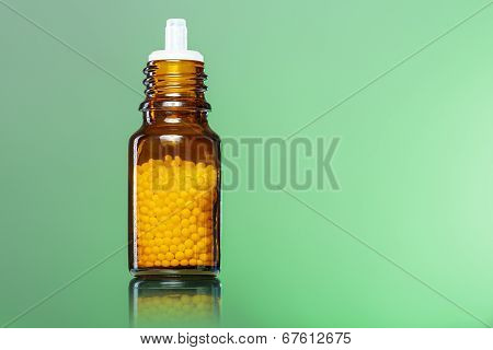 Single Bottle With Homeopathy Globules With Green Background