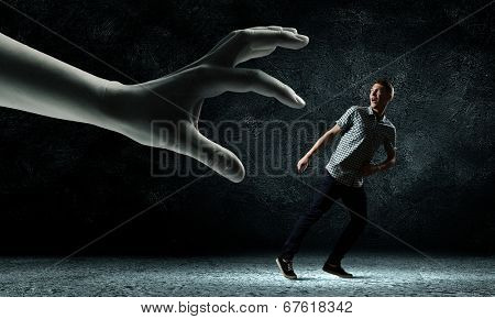 Funny image of young man trying to escape from huge hand