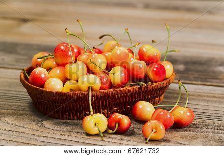 Juicy Golden Rainier Cherries In Basket On Rustic Wood