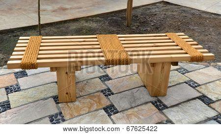 Oriental wooden garden bench with rope standing on stone floor