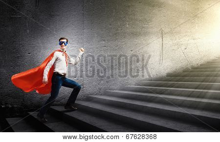 Young confident superman in mask and cape walking on ladder