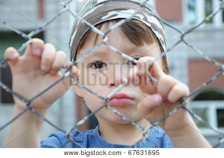 Unhappy Boy Behind Bars