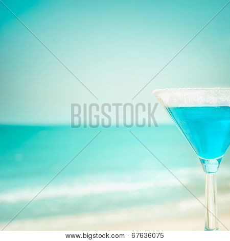 Blue margarita cocktail at tropical ocean beach