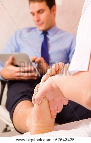 Therapist Massaging Businessman's Foot