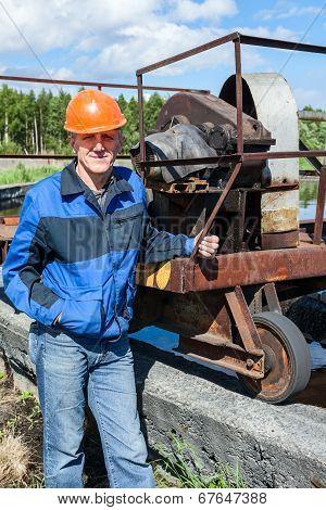 Senior Worker Standing Near Mechanism
