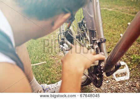 Man Checks Chain Of Bicycle