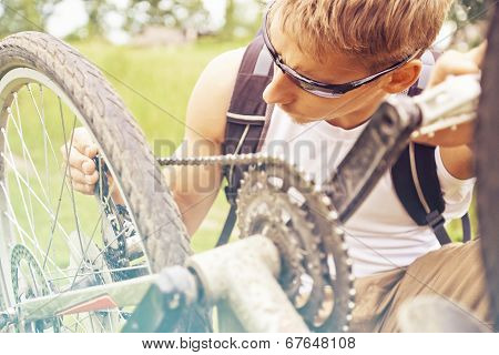 Cyclist Checks Chain Of Bicycle